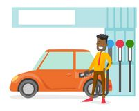 Man filling up fuel into the car at a gas station. Young african-american businessman in suit filling up fuel into the car at the gas station. Cheerful man Royalty Free Stock Photography