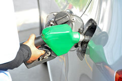 A man filling up the gas tank of a car. Car gas (petrol) filling up stock image