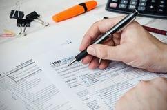 Man filling US tax form stock photo