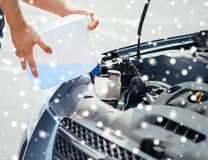 Man filling windscreen water tank Stock Images