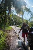 The wreckage of Hurricane Maria. A man fills buckets with water from a roadside spring in Lares, Puerto Rico Stock Photo