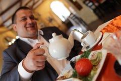 Man fills cup of tea Royalty Free Stock Image
