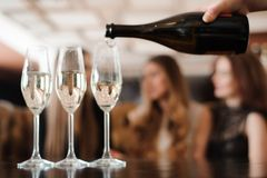 Man fills glasses of champagne for three beautiful young women royalty free stock photography