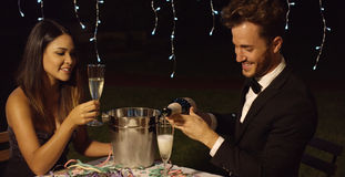 Man fills his glass with champagne to toast Royalty Free Stock Photo