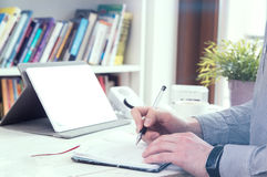 Man fills his planner and a tablet on background Royalty Free Stock Photography
