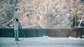 A man fills up the rink with water from a hose stock video footage