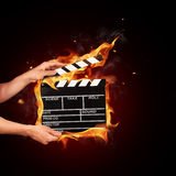 Man with film clapper in fire. Man hands holding film clapper in fire Royalty Free Stock Images