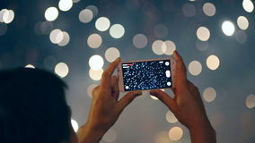Man filming colorful fireworks on his cell phone. stock footage