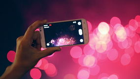 Man filming colorful fireworks on his cell phone. stock video footage