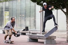 A man filming a skateboarder doing a flip on a bench stock photo