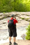 Man filming the stream. Standing on a rock Royalty Free Stock Photos