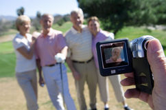 Man filming two mature couples standing on golf course, playing golf, focus on portable digital video recorder in foreground (tilt Stock Image