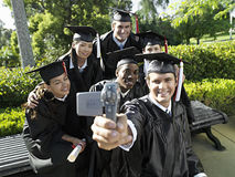 Man filming university students in graduation gowns and mortar boards, using camcorder, smiling Royalty Free Stock Photos
