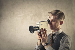 Man filming. Vintage man filming with a video camera Royalty Free Stock Image