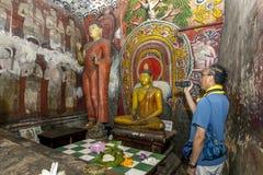 A man films inside Cave One (Devaraja Viharaya) at the Dambulla Cave Temples in Sri Lanka. Royalty Free Stock Photo