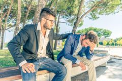 Man with financial or sentimental problems. Young business men supporting a depressed person - Man supporting his friend despairing for his financial problems Stock Photo