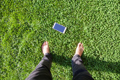 The man find mobile phone on grass. top view of human foot and mobile phone on grass. Royalty Free Stock Photos