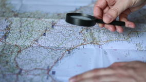 Man Finding a city on a map. Side view stock footage