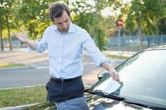 Parking violation ticket fine on windshield. Man finding a ticket fine because of parking violation Royalty Free Stock Photos
