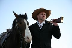 Man in fine old western clothes with horse & rifle. Man gazing out with rifle over his shoulder and holding a saddled bay horse; blue sky behind Royalty Free Stock Photo