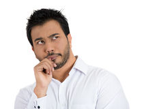 Man with finger in mouth deeply thinking, frowning Stock Image