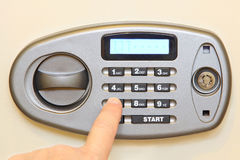 Man finger press button on electronic home safe. Royalty Free Stock Photo