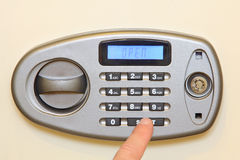 Man finger press start button on electronic home safe. Stock Photography