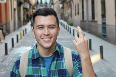 Man with fingers crossed outdoors.  stock image