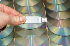 Man fingers holds a USB Universal Serial Bus stick in front on a stack of cd compact disc and dvd digital versatile optical disc royalty free stock photo