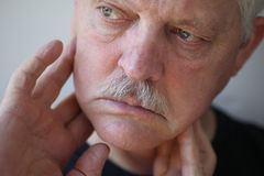 Man with fingers on painful jaw. Senior man touches his sore jaw area royalty free stock images