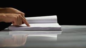 Man fingers read Braille writing. Black background. Side view. Man fingers read Braille writing on a white book. Black background. Side view stock video