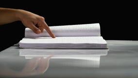 Man fingers read Braille writing. Black background. Side view. Man fingers read Braille writing on a white book. Black background. Side view stock video footage