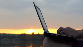 Man Fingers Type on a pc Keyboard Outdoor on a River Bank at Sunset. A Splendid Close-Up of Male Fingers Which Type on a Gray pc Keyboard Outdoor on a River Bank stock video footage