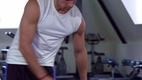 Man finishes the exercise. Attractive sportsman finishing his exercise at the gym. Strong male athlete stopping to do tricep dumbell kickbacks. Muscular stock footage