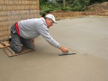 Man finishing concrete slab. Using trowel stock photos
