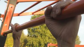 Man finishing doing pull-ups on crossbar, give-up, sports activity hands closeup. Stock footage stock video