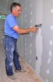 Man finishing drywall. Man using trowel to finish seam between drywall panels royalty free stock photos