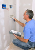 Man finishing drywall. Man using drywall knife to finish seam between drywall sheets stock photo