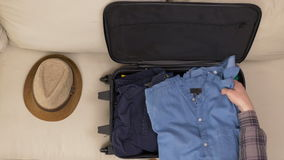 Man finishing packing clothes into travel bag. Man finishing packing clothes into a travel bag stock video footage