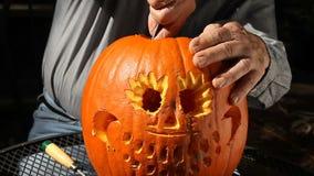 Man finishing up Halloween pumpkin stock video footage