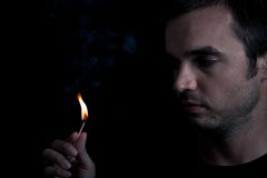 Man and fire. Dramatic portrait of man lighting safety match, over black background stock images