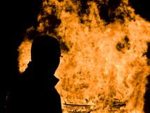 Man and fire. Silhouette of a man standing in front of a fire royalty free stock image