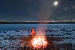 Man by fire watch moon icy Lake Laberge YT Canada stock photography