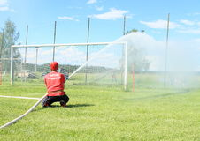 Man firefighter. Man on fire attack - firefighter on competition spouting water from hose to the target and kids - boys and girls soaking wet behind (The 18th of stock image