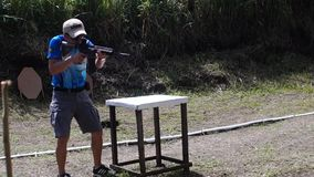 Man fires rifle during practice training in practical shooting. San Pablo City, Laguna, Philippines - July 29, 2013: Man fires rifle during practice training in stock video footage