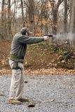 Man Firing Pistol. Man firing a black pistol. Smoke exits from the barrel. In the chamber is a brass / yellow glimmer of the next round loading. Above and Stock Photos