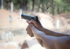Man firing pistol at firing range. A bullet shell flies out of a handgun while a man takes target practice at a firing range Royalty Free Stock Image