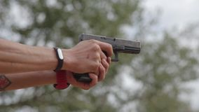FullHD footage. Man firing from pistol, low angle view stock footage