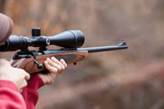 Man Firing a Rifle. Rifle with a scope firing in the woods Stock Photos