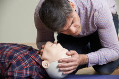 Man In First Aid Class Checking Airway On CPR Dummy Stock Photos
